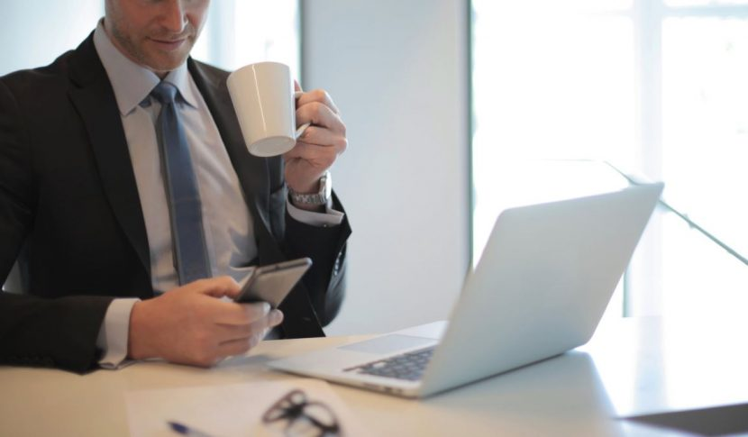 Man sat at laptop with cup of tea
